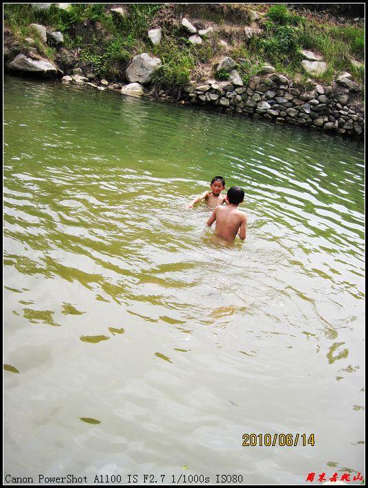 农村小孩子们尽情在水塘逮鱼玩水
